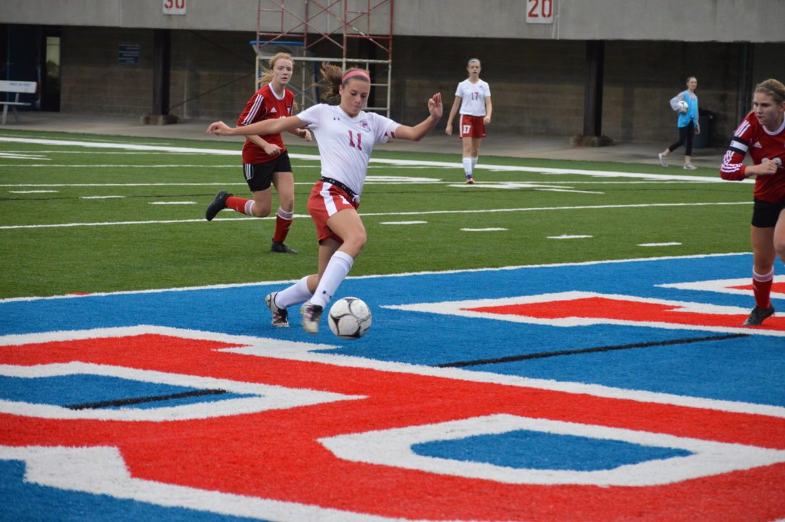 Photo by Cody Tomer Wheeling Park senior Morgan Glass (11) connects with the ball as she scores her second goal of the match on Senior Night at Wheeling Island Stadium.
