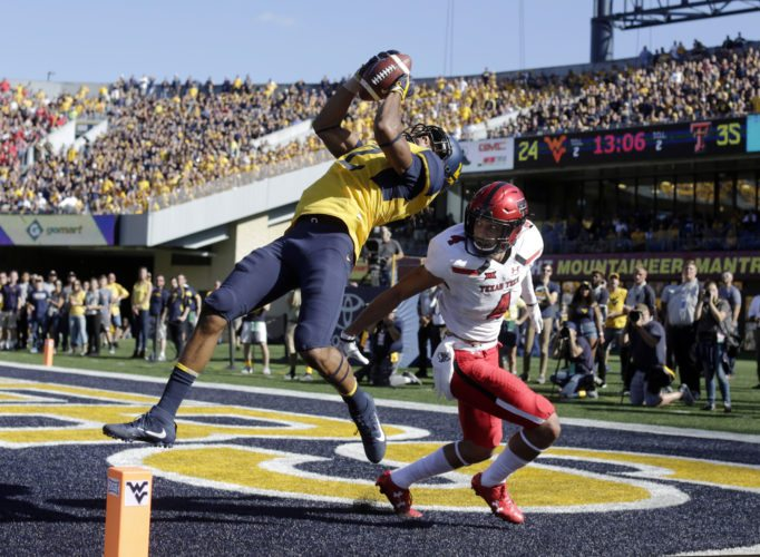 West Virginia wide receiver Ka'Raun White (2) catches a touchdown pass in front of Texas Tech defensive back Desmon Smith (4) during the second half of an NCAA college football game, Saturday, Oct. 14, 2017, in Morgantown, W.Va. (AP Photo/Raymond Thompson)