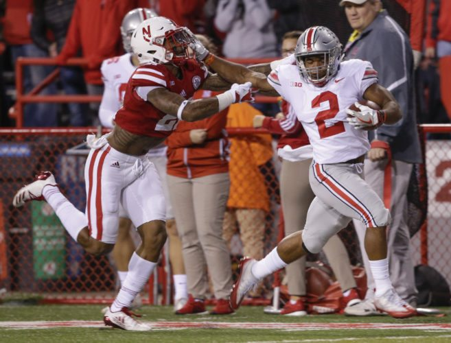 Ohio State running back J.K. Dobbins (2) stiff-arms Nebraska defensive back Lamar Jackson (21) as he runs for a touchdown during the first half of an NCAA college football game in Lincoln, Neb., Saturday, Oct. 14, 2017. (AP Photo/Nati Harnik)