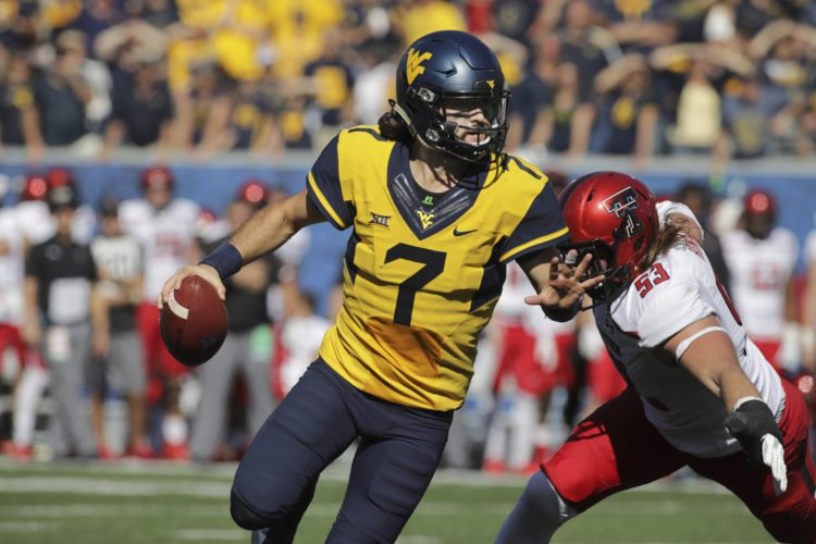 West Virginia quarterback Will Grier (7) scrambles to avoid a Texas Tech defensive lineman Eli Howard (53) during the second half of an NCAA college football game, Saturday, Oct. 14, 2017, in Morgantown, W.Va. West Virginia defeated Texas Tech 46-35. (AP Photo/Raymond Thompson)