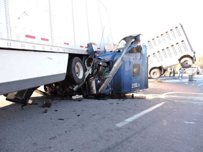 The cab of a tractor-trailer rests beneath the trailer of another semi-truck that it struck from behind on Interstate 70 east at St. Clairsville early Tuesday. The trailer that was attached to the cab can be seen in the background, where it went over an embankment.