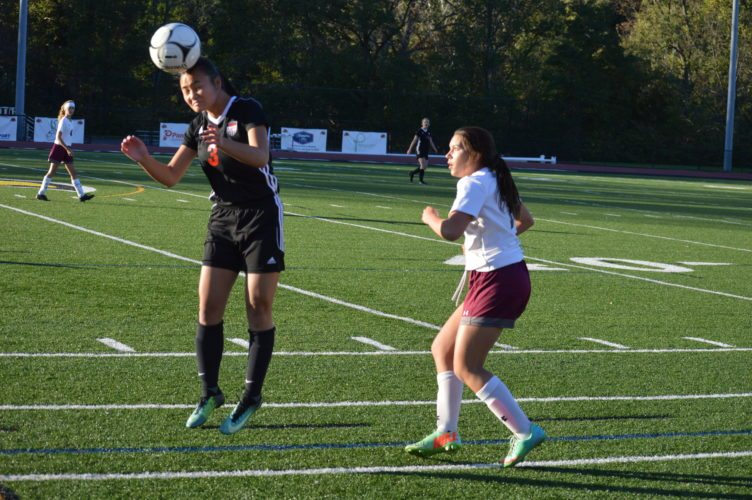 Photo by Cody Tomer Weir's Julia Gianni heads a pass from a teammate, while Wheeling Central's Maria Dzmura looks on.
