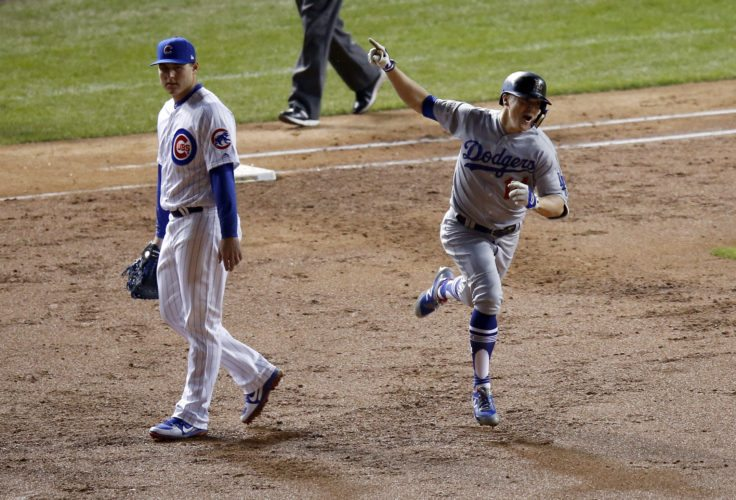 Los Angeles Dodgers' Enrique Hernandez (14) celebrates as he runs bases after hitting a grand slam during the third inning of Game 5 of baseball's National League Championship Series, Thursday, Oct. 19, 2017, in Chicago. At left is Chicago Cubs first baseman Anthony Rizzo. (AP Photo/Charles Rex Arbogast)