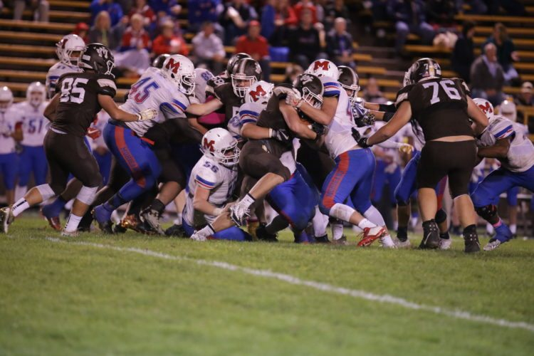 Photo by Alex Kozlowski John Marshall running back Dereck Hess is gobbled up by a host of Morgantown defenders Friday in Moundsville. The Monarchs won, 21-10, to clinch their first playoff birth since 2007.