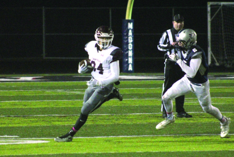 Photo by Joe Catullo Wheeling Central's Logan Wells runs the ball while Madonna's Chayce Lemley goes for a tackle during Saturday night's game.
