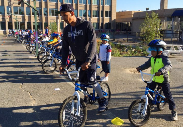 In this Oct. 3, 2017, photo, second-graders learn to ride bikes on the school yard from physical education teacher Terrance Chavis at Seaton Elementary School in Washington. At a time when elementary and high schools are all about getting students ready for college or jobs, physical education teachers are being urged to look beyond graduation, too, to make lifelong movers out of even the least competitive kids. (AP Photo/Maria Danilova)