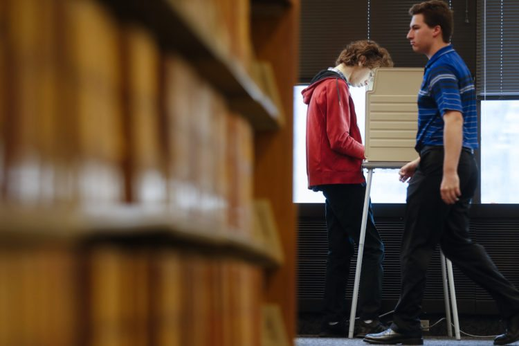 A voter fills out his ballot at a polling station at the University of Cincinnati, Tuesday, Nov. 7, 2017, in Cincinnati. Ohio voters will decide ballot issues on Tuesday that would place limits on drug prices and expand victims' rights in criminal proceedings, along with several mayoral races. (AP Photo/John Minchillo)
