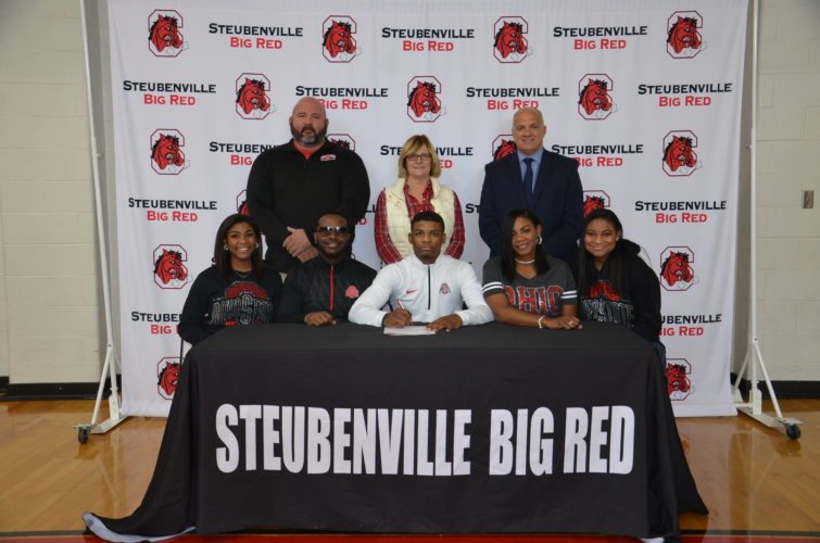 Photo by Kim North Steubenville senior Jashon Hubbard signed a National Letter of Intent on Wednesday morning inside the Crimson Center to attend Ohio State University on a wrestling scholarship. Pictured, sitting from left, are Jaliyah Hubbard (sister), Jesse Hubbard (father), Jashon, Martina Mayo (mother) and Jasmine (sister). Back row, are Steubenville coach Mike Blackburn, Steubenville athletics director Lynn Meyer and Steubenville principal Ted Gorman.