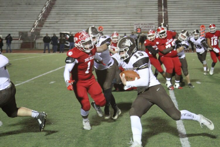 Photo by Tom Perry John Marshall's Nick Coulter (15) carries the ball as Parkersburg's Zion Atkinson (1) tries to bring him down during Friday's Class AAA playoff football game at Stadium Field in Parkersburg.