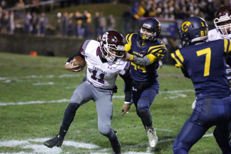 Photo by Alex Kozlowski Wheeling Central's Curtis McGhee III(11) is grabbed by the facemask by Cameron's Matthew Ritchea (44) during Friday's playoff game in Cameron.
