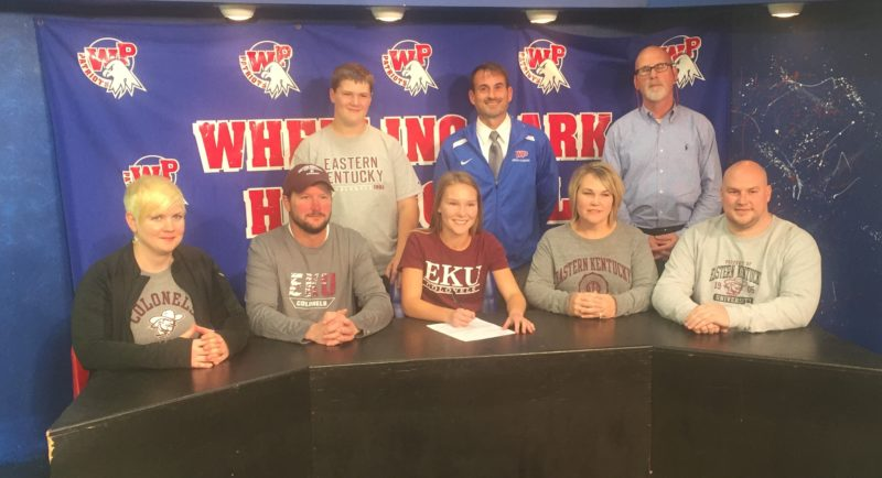 Photo by Seth Staskey Wheeling Park senior Beighley Ayers signed her National Letter of Intent to continue her track and cross country careers at Division I Eastern Kentucky University. Pictured, from left, are stepmother Carolyn Ayers, father Kevin Ayers, Beighley Ayers, mother Mindy Martin and step father Scott Martin. Standing, from left, are brother Keegan Ayers, Wheeling Park cross country coach Jacob Galik and Athletics Director Dwaine Rodgers.