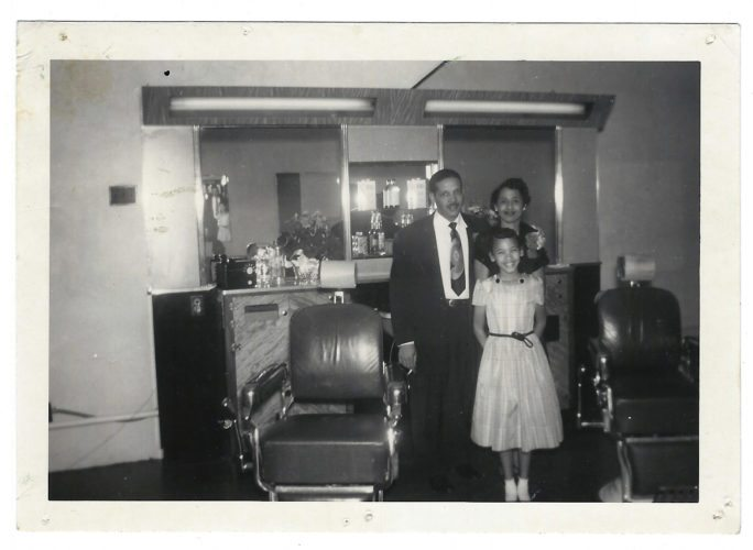 This historical family photo belonging to Dr. Heather R. Parker, left, is an example of how looking at the background of a photo provides insight into the family and the time period. Pictured are    Parker's grandfather John Pitts, who owned the barber shop where the picture was taken in the early 1950s; her         grandmother Isabelle Pitts and her mother Sharon Pitts.
