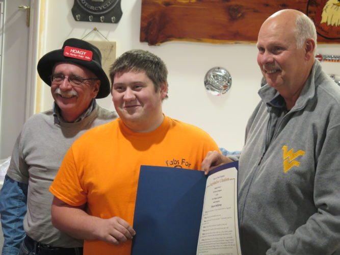 "Photo by Alan Olson Magnolia High School junior Dexton McKinney, center, is honored by West Virginia Delegate Mike Ferro, D-Marshall, right, for his work in collecting soda tabs for charity through Hoagy's Heroes. At left is Robert ""Hoagy"" Carmichael."