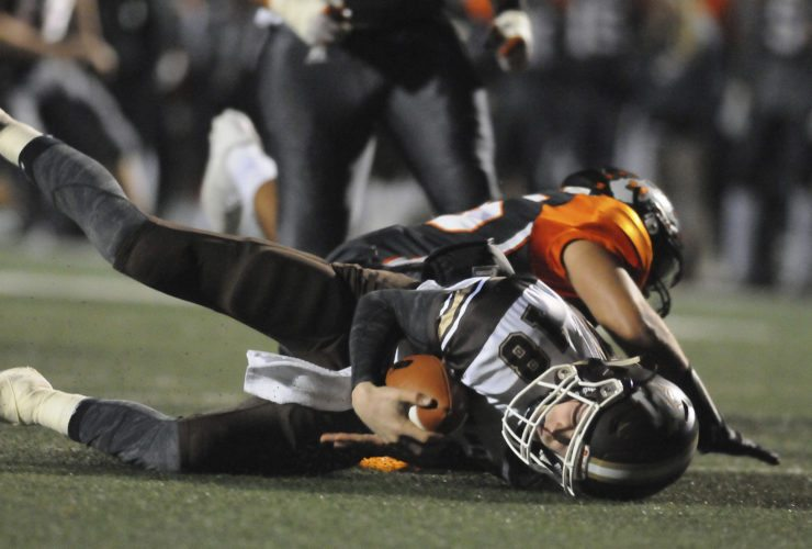18 JM@Mart FB2 ra 11-17-17 John Marshall Quarterback Jordan Wood (18) gets sacked by Martinsburg Linebacker Mikey Jackson Jr. (25) during 1st quarter action of the Class AAA Quarterfinal game Friday night in Martinsburg. See more photos on CU.journal-news.net. (Journal Photo by Ron Agnir)