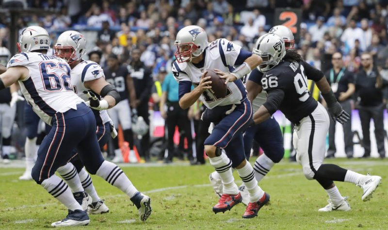 New England Patriots quarterback Tom Brady, center, scrambles against the Oakland Raiders during the first half of an NFL football game Sunday, Nov. 19, 2017, in Mexico City. (AP Photo/Rebecca Blackwell)