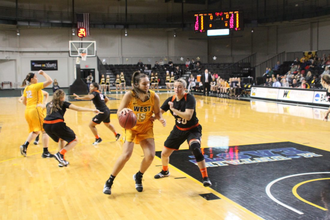 Photo Provided by WestLiberty Athletics West Liberty's Marissa Brown (15) drives to the basket while West Virginia Wesleyan's Mari Stewart guards.