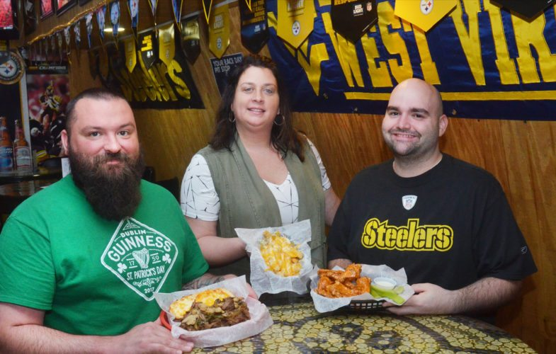 Photo by Scott McCloskey  19th Hole head cook Chas Howell, owner Angie Szalay and assistant manager Luke Tolbert display the always popular menu choices — a steak filet hoagie, cheese fries and wings.