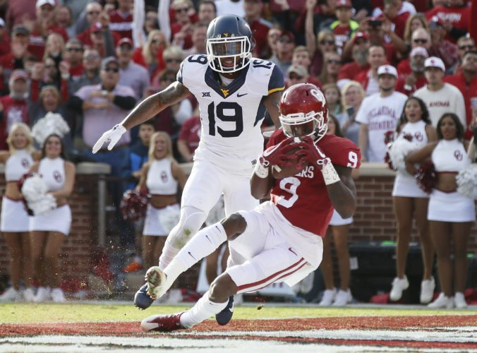 Oklahoma wide receiver CeeDee Lamb (9) falls into the end zone with a touchdown in front of West Virginia cornerback Elijah Battle (19) in the first quarter of an NCAA college football game in Norman, Okla., Saturday, Nov. 25, 2017. (AP Photo/Sue Ogrocki)
