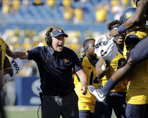 FILE - In this Oct. 14, 2017, file photo, West Virginia coach Dana Holgorsen celebrates a touchdown with his team during the second half of an NCAA college football game against Texas Tech in Morgantown, W.Va. West Virginia faces Texas this week. While the Mountaineers will need help to get into the Big 12 championship game, they first to have to win their own games. Plus, Texas is still trying to get bowl eligible in coach Tom Herman's first season. (AP Photo/Raymond Thompson, File)