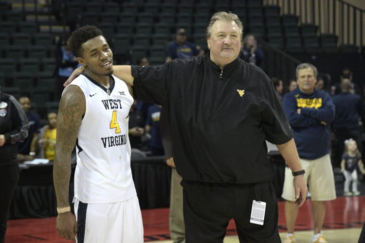 West Virginia head coach Bob Huggins, right, hugs guard Daxter Miles Jr. (4) after earning a 83-79 win over Missouri in an NCAA college basketball championship game at the AdvoCare Invitational tournament Monday, Nov. 27, 2017, in Lake Buena Vista, Fla. (AP Photo/Phelan M. Ebenhack)