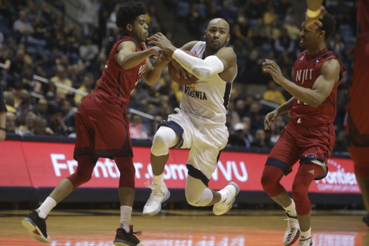 West Virginia guard Jevon Carter (2) splits NJIT guards Diandre Wilson (15) and Shyquan Gibbs (11) during the second half of an NCAA college basketball game Thursday, Nov. 30, 2017, in Morgantown, W.Va. West Virginia won 102-69. (AP Photo/Raymond Thompson)