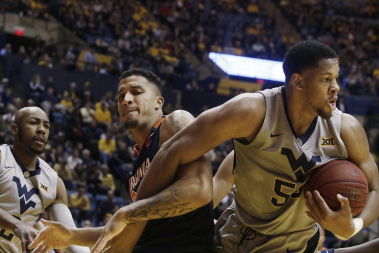Virginia forward Isaiah Wilkins (21) West Virginia forward Sagaba Konate, right, struggle for control of a rebound during the first half of an NCAA college basketball game Tuesday Dec. 5, 2017, in Morgantown, W.Va. (AP Photo/Raymond Thompson)
