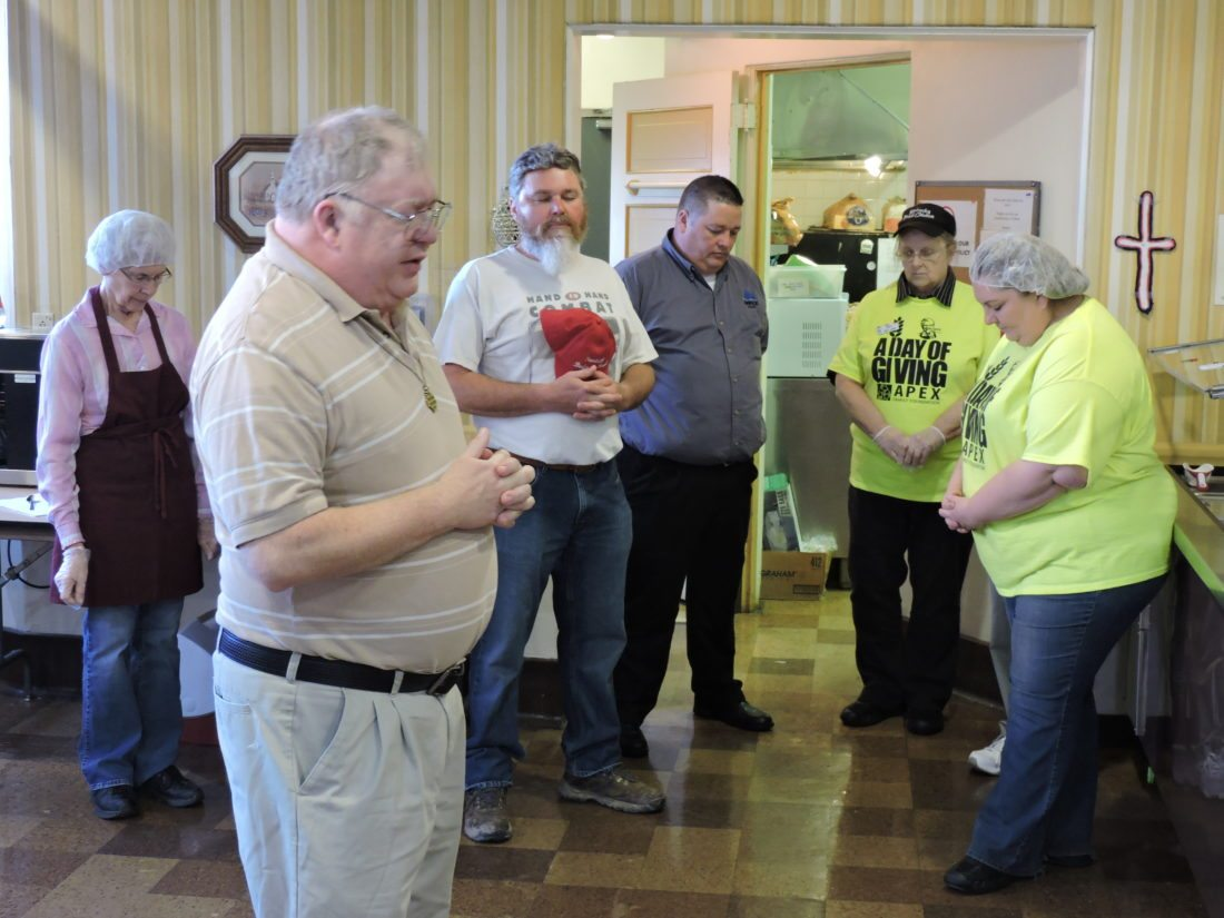 Photo by Alan Olson The Rev. Dennis Mehaffie leads volunteers in prayer before serving lunch at Simpson United Methodist Church's Feeding Body and Soul Community Kitchen on Wednesday.