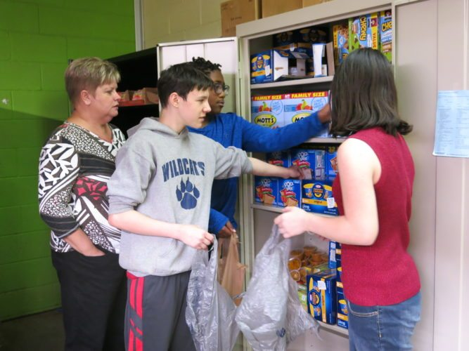 Photo by Joselyn King Wheeling Middle School teacher Renee Marchese, left, and students Gary McCormick, Kievion'tai Saunders and Emma Davis, help pack bags of food from the Wildcat Food Pantry at the school.