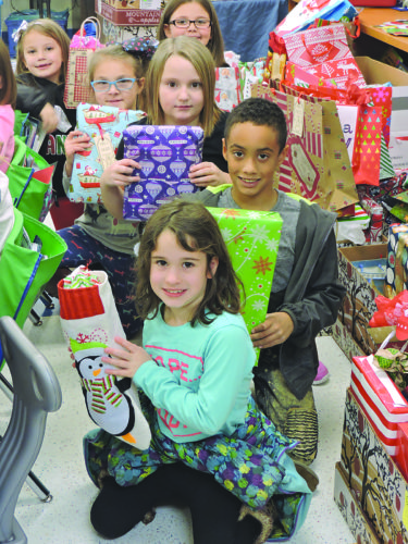 Photo by Alan Olson Hilltop Elementary School students showing off their hand-wrapped gifts of pajamas for local families in need, from front to back, are Alexis Kimberly, Ty Clemens, Saranee Burnt, Gracie Adams, Macy Baker and Ashton Waller.
