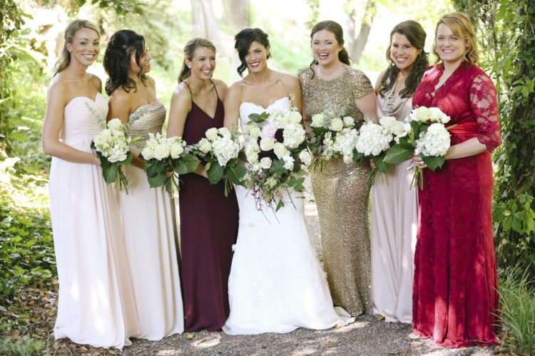 In this May 2016 photo provided by Leah Moyers Photography, the bridal party of Sydney Broadhead of Nashville, Tenn., poses at her wedding in Ashville, N.C. Broadhead allowed her bridesmaids to choose their own dresses, though she stayed in the loop on their plans and was the final arbiter. Mismatching bridesmaids dresses has become more popular in recent years. (Leah Moyers Photography via AP)