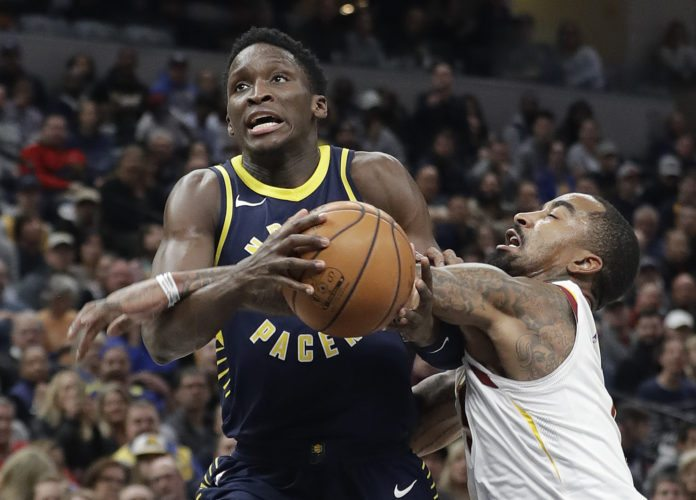 Indiana Pacers' Victor Oladipo (4) is fouled by Cleveland Cavaliers' JR Smith during the second half of an NBA basketball game Friday, Dec. 8, 2017, in Indianapolis. The Pacers won 106-102. (AP Photo/Darron Cummings)