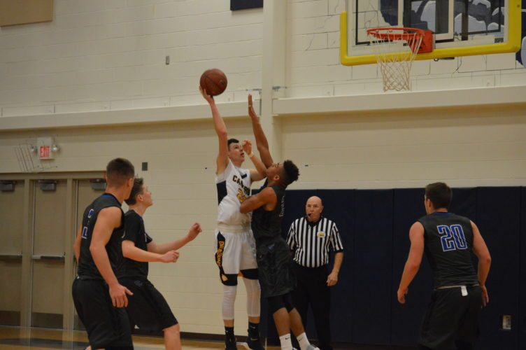 By Kyle Lutz Cameron's Travis Mickey goes up for a shot while Tyler Consolidated's Mark Rucker defends during Friday night's game at Cameron High School. Looking on is referee Mike Coyne.