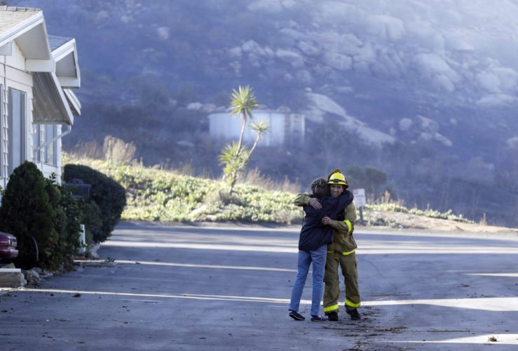 Firefighter Simon Garcia, of Heartland Fire Dept., gets a hug from a woman who did not give her name after she arrived to find her house was intact in the Rancho Monserate Country Club, Friday, Dec. 8, 2017, in Fallbrook, Calif. The wind-swept blazes have forced tens of thousands of evacuations and destroyed dozens of homes in Southern California. (AP Photo/Gregory Bull)