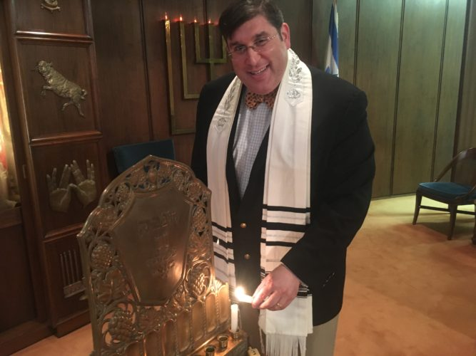 Photo by Jessica Broverman Rabbi Joshua Lief of Temple Shalom in Wheeling lights a candle for the first night of Hanukkah, which begins Tuesday and continues through Dec. 20.
