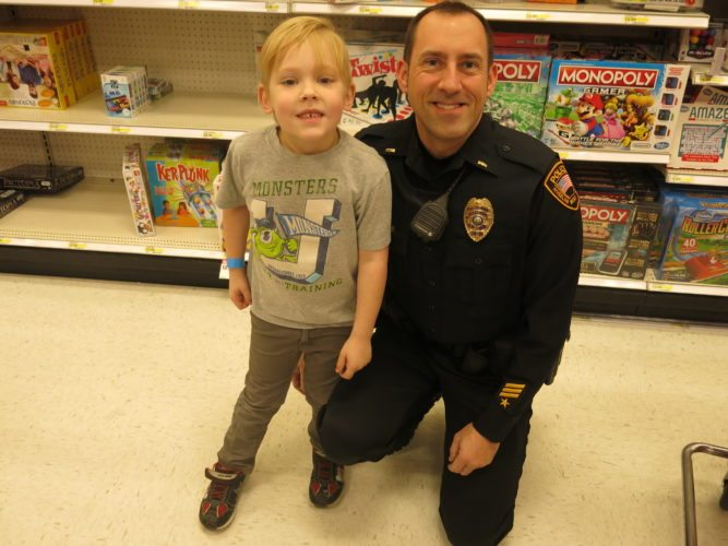 "Photo by Jessica Broverman  Lt. Micah Zinn of the Wheeling Police Department and Colton Thomas shop in the gaming aisle of Target at The Highlands during Sunday's ""Shop With a Cop"" event."