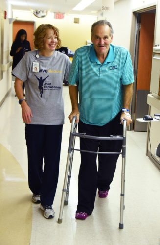 Photo Provided The day after receiving a free total knee replacement, Richard Thompson of Wheeling walks down the hall with Shannan Lawrence, a physical therapist at WVU Medicine J.W. Ruby Memorial Hospital in Morgantown.