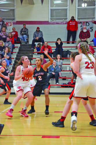 Photo by Kim North St. Clairsville's Keri Klinkosi attempts a shot while Bellaire's Katrina Davis defends during Monday's game.
