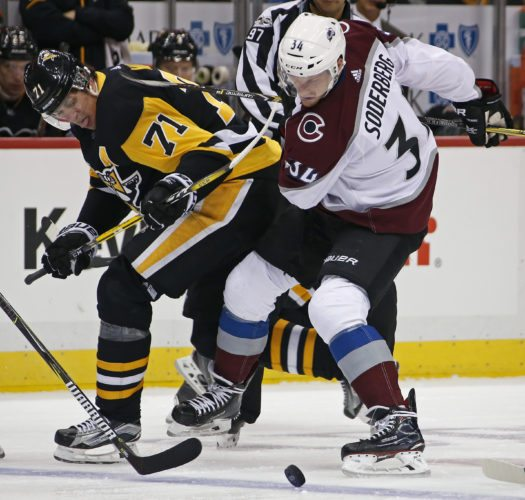 Pittsburgh Penguins' Evgeni Malkin (71) and Colorado Avalanche's Carl Soderberg (34) battle for the puck during the second period of an NHL hockey game in Pittsburgh, Monday, Dec. 11, 2017. (AP Photo/Gene J. Puskar)
