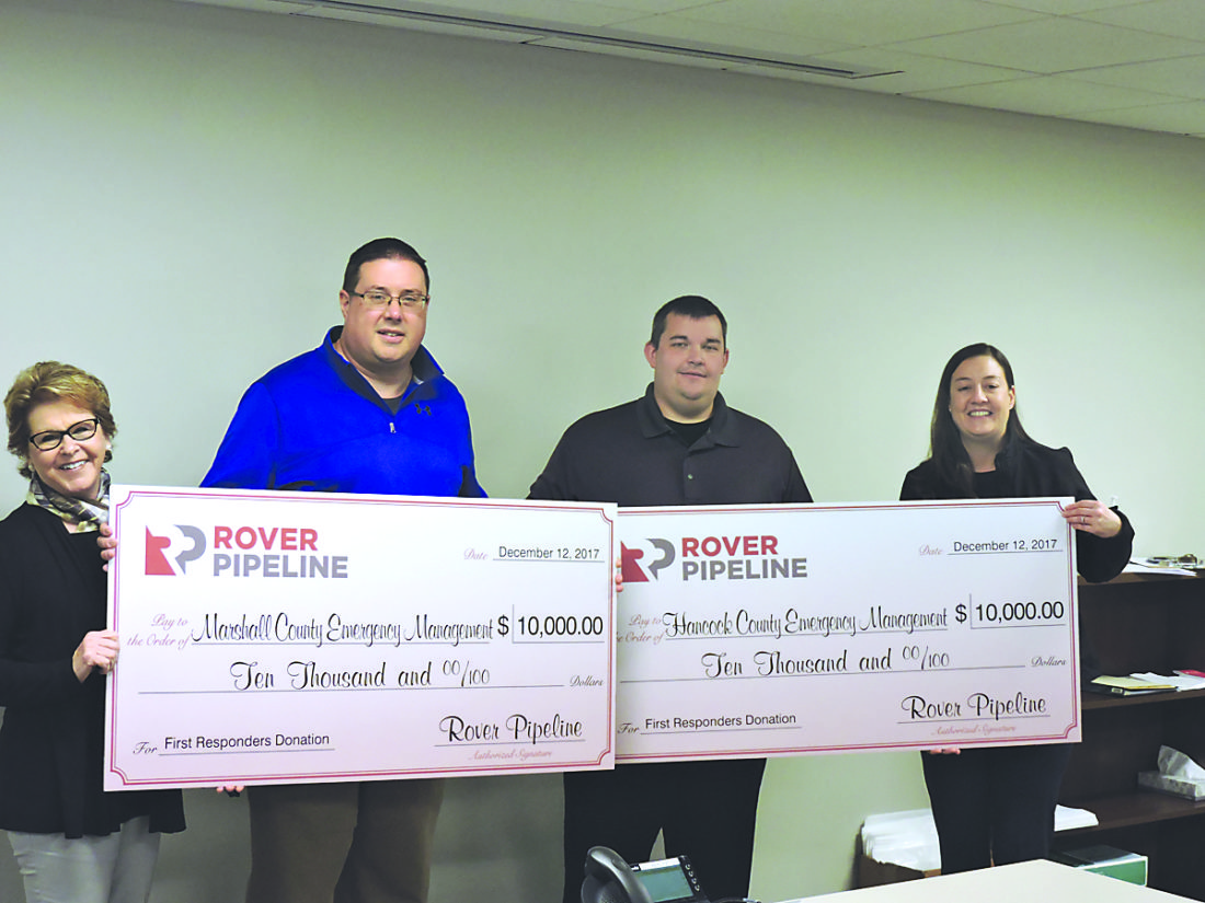Photo by Alan Olson Rover Pipeline representatives Susan King, left, and Alexis Daniel, right, present checks to Marshall and Hancock County OEM directors Tom Hart, center-left, and Jeremy Oberman, center-right.