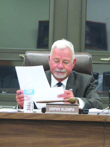 Photo by Joselyn King Ohio County Commission President Orphy Klempa reviews documents during Tuesday night's commission meeting.