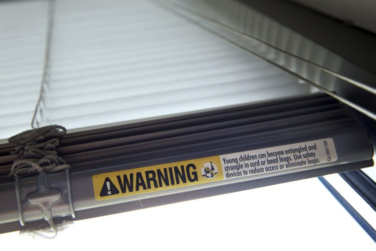 AP Photo A warning label of strangulation risks from mini blind cords in Washington, D.C., is shown on this set of min blinds. According to a study released Monday, children's injuries and deaths from window blinds have not stalled despite decades of safety concerns.