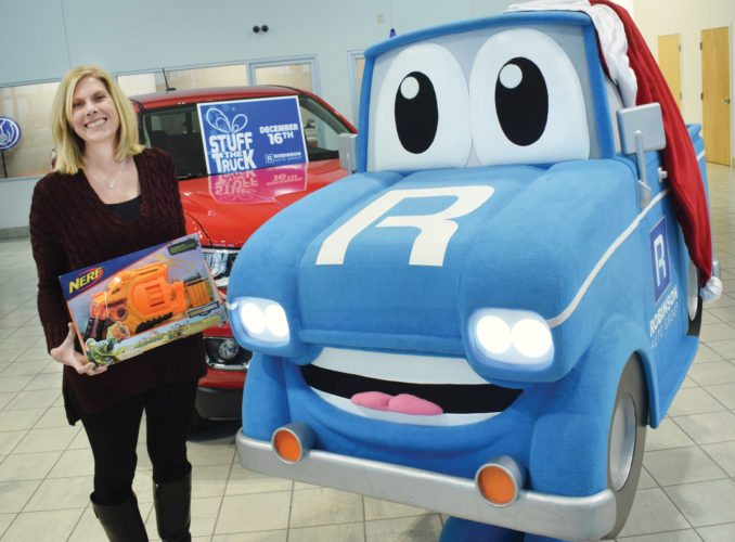 "Photo by Scott McCloskey Roberta Robinson Olejasz of Bob Robinson Chevrolet-Cadillac-Buick-GMC invites the public to donate a toy or clothing item to Robinson Auto Group's 2017 ""Stuff the Truck"" event this week at the Highlands."