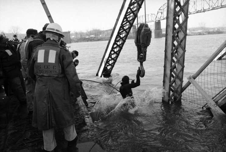 FILE- In this Dec. 15, 1967 file photo, a diver prepares to inspect the wreckage from the Silver Bridge collapse in Point Pleasant, W.Va.  Fifty years ago Friday, Dec. 15, 2017, the collapse of the Silver Bridge killed 46 people.  (The Herald-Dispatch via AP, File)