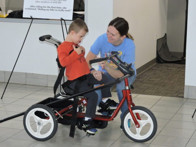 "Photo by Casey Junkins Weirton resident Amber Witschey and her son, 7-year-old Colton, check out a bicycle adapted for use by children with special needs during the ""My Bike"" event Thursday at Bob Robinson Chevrolet Buick GMC Cadillac."