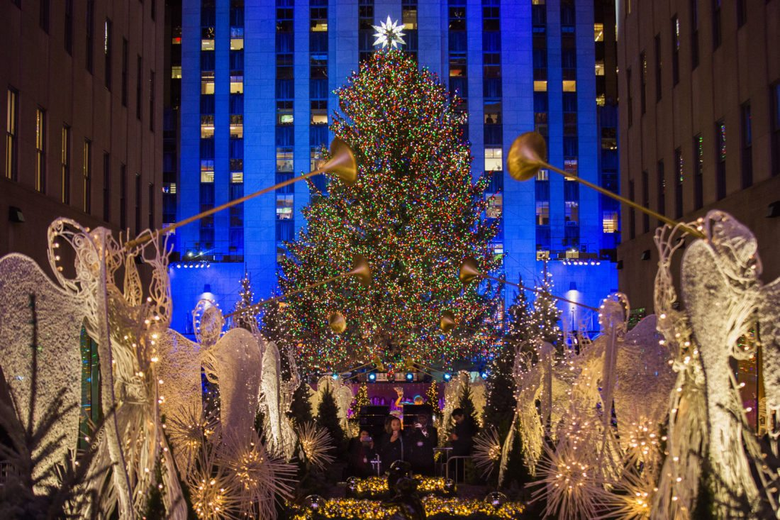 the lighted rockefeller center christmas tree stands tall as people take photos of it and the holiday decorations at rockefeller center during the 85th
