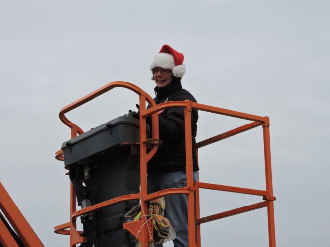 Wheeling City  Councilwoman Wendy Scatterday works the controls of a bucket lift truck during Operation Toy Lift at the Ohio Valley Mall.  Photo by Heather Ziegler