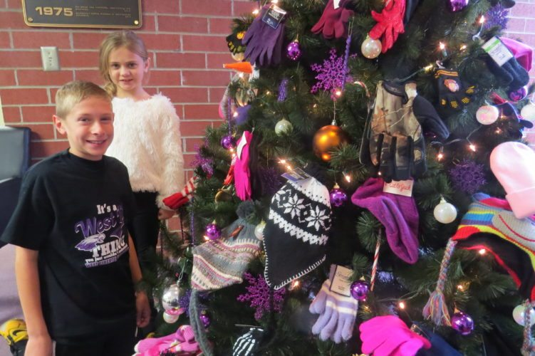 Photo Provided West Liberty Elementary School students Kevin Whitmire, left, and Destyona McGarry stand with the school's mitten tree, adorned with items collected by students for donation to the Soup Kitchen of Greater Wheeling.