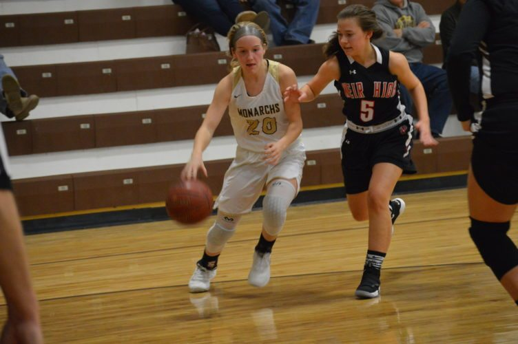 John  Marshall's Anna Blake (20) drives to the basket as Weir's Taylor Webster defends Wednesday in Moundsville.     Photo by  Josh Strope
