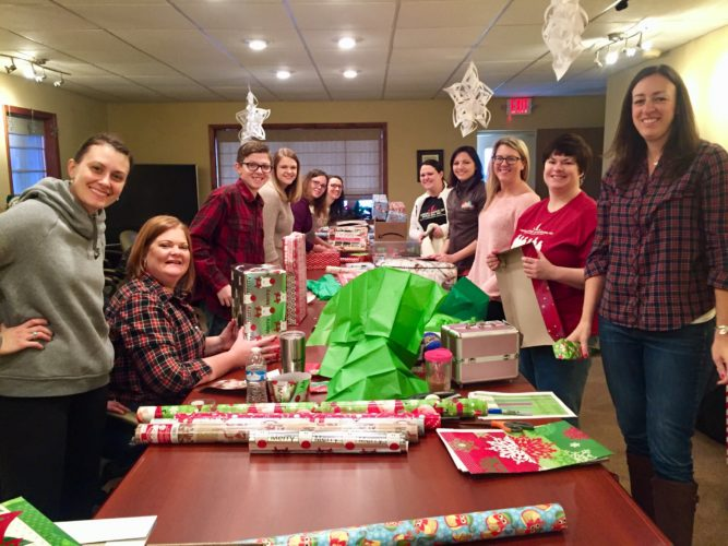 Photo Provided Members of the Junior League of Wheeling help wrap gifts for the young women and children served by Crittenton Services.