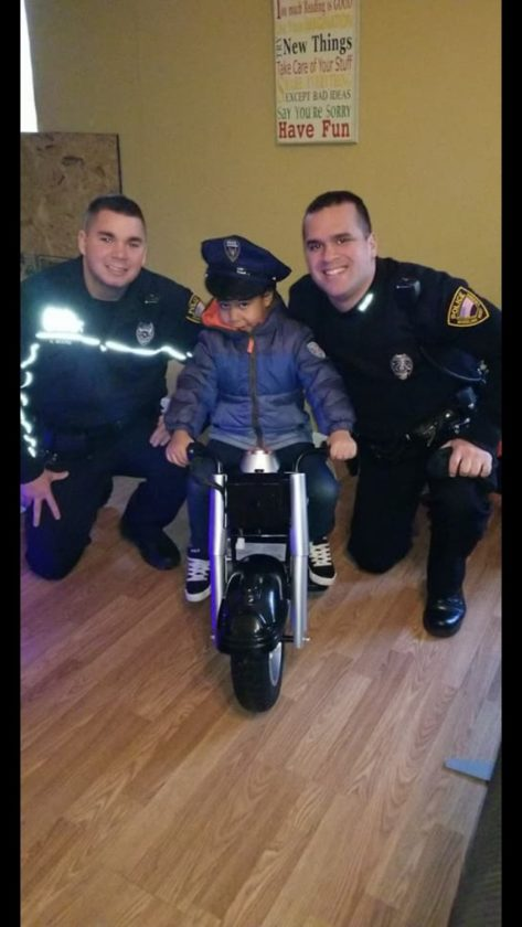 Photo provided by Mary Musap Wheeling Police Officer Harry Myers, left, Jarren Dowd, center, and Officer Ryan Moore, are shown after using the siren in the police cruiser and opening gifts for the little boy from the Wheeling Police Department.